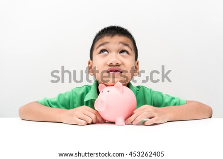 asian boy happy with piggy saving coins, looking up - stock photo
