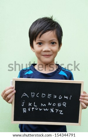 Asian boy holding a chalkboard with ABC - stock photo