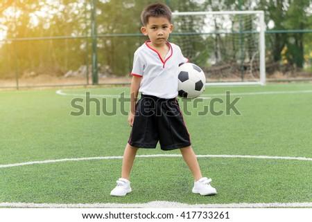 Asian boy holding a football on the football field. - stock photo
