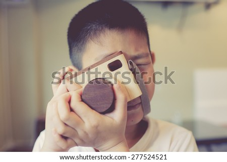 Asian boy holding a wooden camera toy. - stock photo