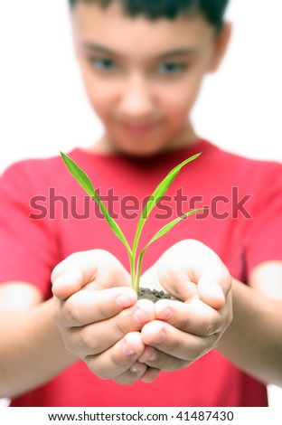 asian boy holding green plant in hands - stock photo
