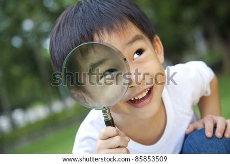 asian boy holding magnifier - stock photo