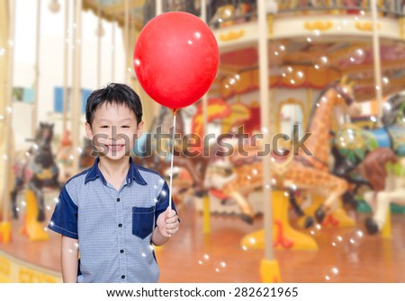 Asian boy holding red balloon in front of merry go round - stock photo