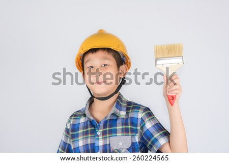 Asian boy in a protective helmet with brush in his hand - stock photo