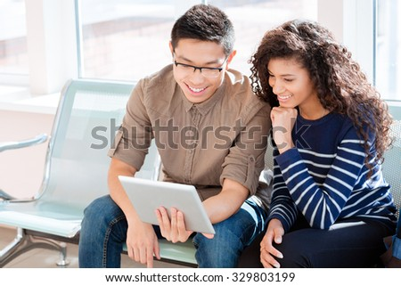 Asian boy in black glasses and african american curly girl girl are using tablet computer - stock photo