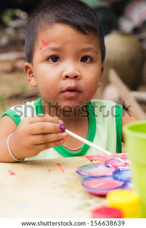 Asian boy in countryside thailand. painting in outdoors - stock photo