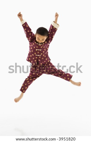 Asian boy in traditional attire jumping into air excitedly against white background. - stock photo