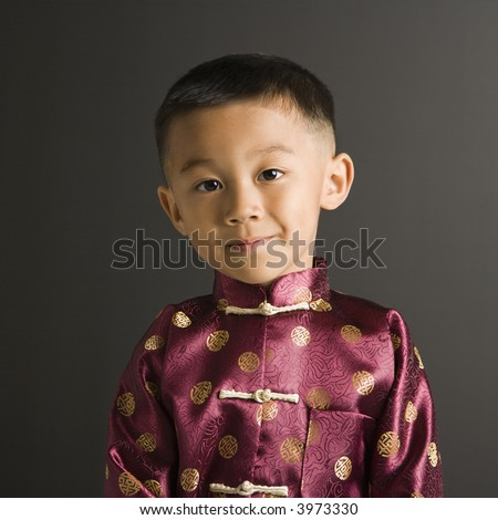 Asian boy in traditional attire standing against black background. - stock photo