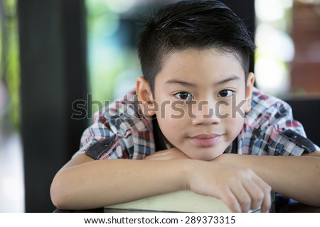 Asian boy is little smile and looking camera - stock photo