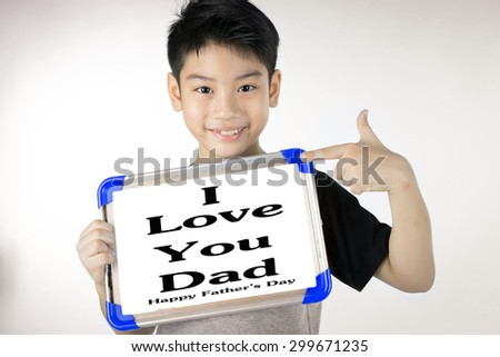 Asian boy is little smile with blank white board and looking camera on gray background, Word is I Love Dad. - stock photo