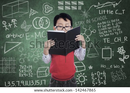 Asian boy is reading a book in classroom - stock photo