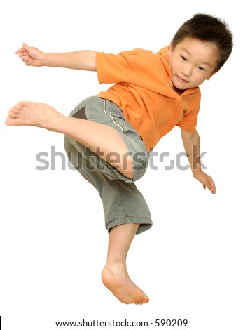 Asian boy jumping on bed doing kung fu kick on white