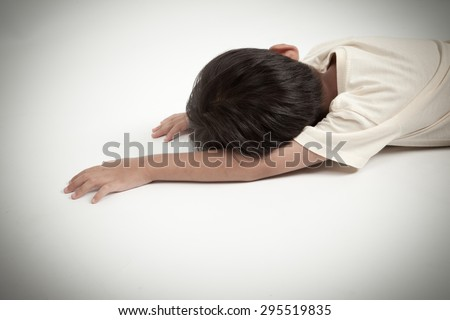asian boy kid lying down on white floor like accident or fainting  - stock photo