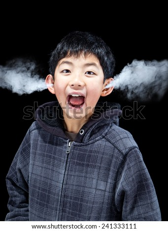 Asian boy letting off steam as he expresses his emotions. Concept of stress, anger, frustration and extreme emotions. - stock photo