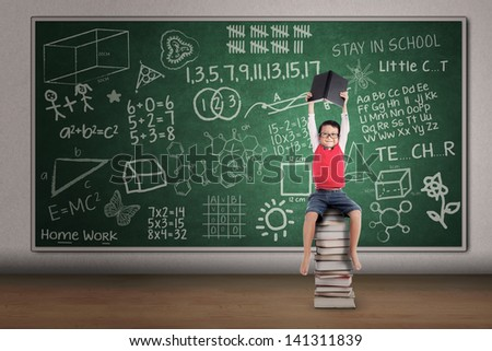 Asian boy lifting a book while sitting on stack of books in classroom - stock photo