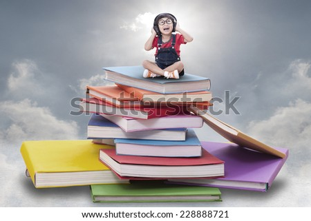 Asian boy listening to the music and sitting on pile of books  - stock photo