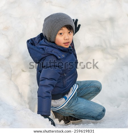 Asian boy outdoors - playing with snow