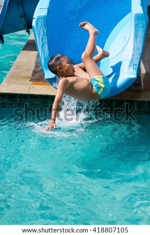 Asian Boy play blue slider into the pool - stock photo