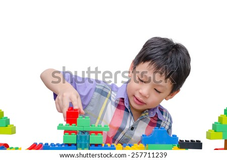 Asian boy playing construction block over white background