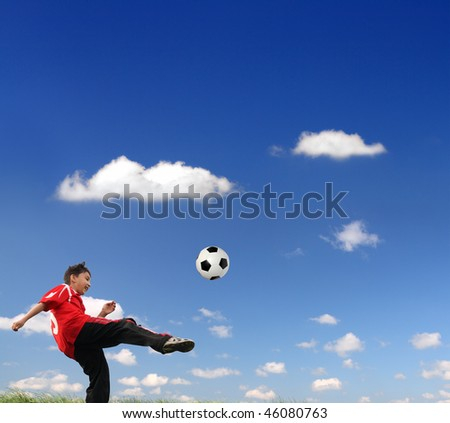 asian boy playing football under blue sky - stock photo