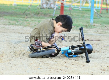 Asian boy playing near his bicycle in the park - stock photo