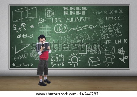 Asian boy reading book with written chalkboard, full length shot - stock photo