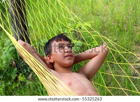 asian boy relaxing in hammock outdoors - stock photo