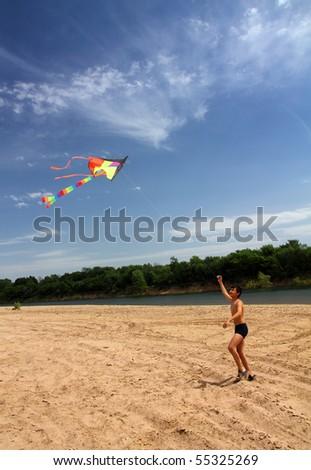 asian boy running kite on river beach - stock photo