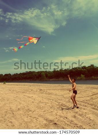 asian boy running kite on river beach - vintage retro style - stock photo