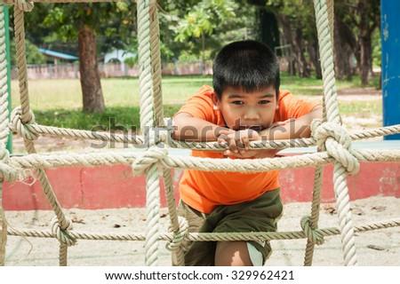 asian boy sitting alone at playground - stock photo