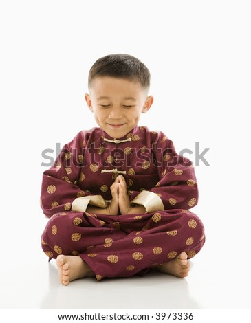 Asian boy sitting meditating against white background in traditional  attire. - stock photo