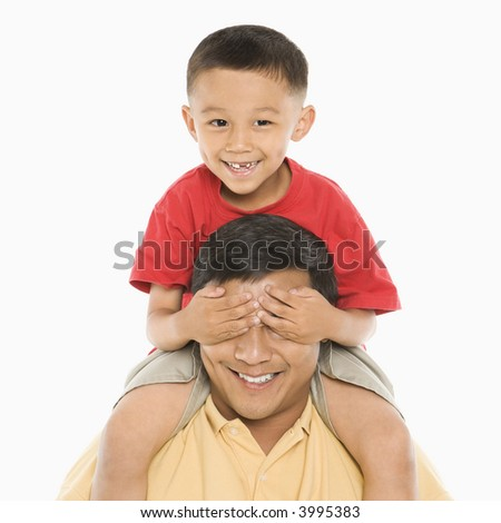 Asian boy sitting on father's shoulders with hands over his eyes in front of white background. - stock photo