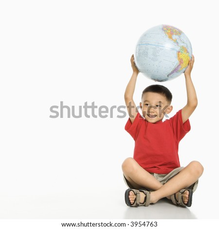 Asian boy sitting on floor holding Earth globe over his head.