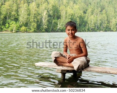 asian boy sitting on stage in lake portrait - stock photo