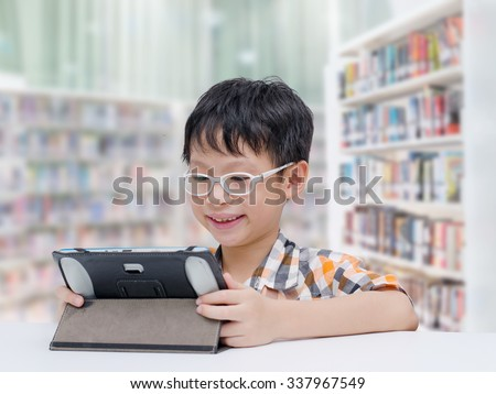 Asian boy student searching information by tablet computer in school library - stock photo