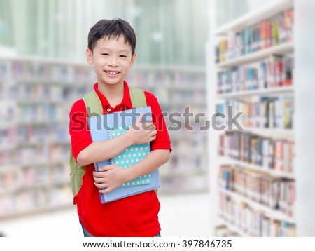 Asian boy student standing in school library - stock photo