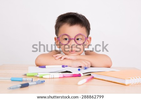 asian boy student to do homework at a table on a white background - stock photo