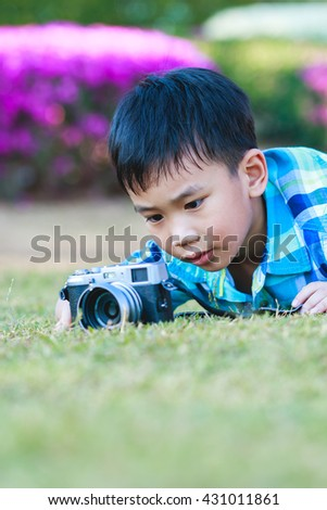 Asian boy taking photo by vintage film camera on blurred nature background at the day time. Adorable child enjoying at park. Outdoors. - stock photo