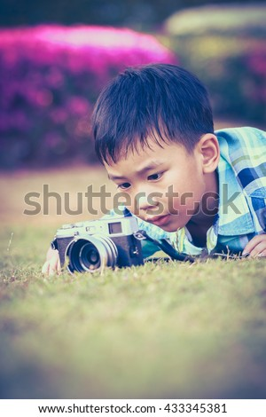 Asian boy taking photo by vintage film camera on blurred nature background at the day time. Adorable child enjoying at park. Outdoors. Vignette and vintage tone. - stock photo