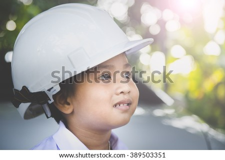 Asian boy wear safty helmet are thinking something about his future , engineering concept. Vintage Tone