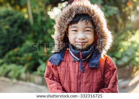asian boy wearing a red colorful sweater in the garden - stock photo