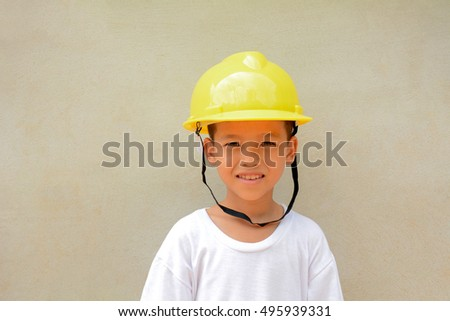 Asian boy wearing helmet.Cement gray background