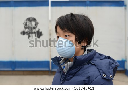 Asian boy wearing mouth mask against air pollution  - stock photo