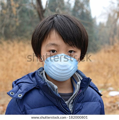 Asian boy wearing mouth mask standing in front of dry forest affected by pollution  - stock photo