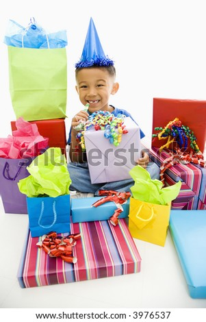 Asian boy wearing party hat sitting with pile of wrapped presents.