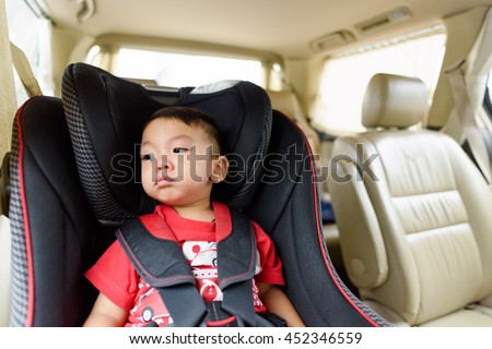 Asian boy wearing red T-shirt in safety car seat. Unhappy child crying.