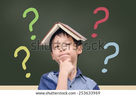 Asian boy with book on head thinking in front of chalkboard with question mark - stock photo