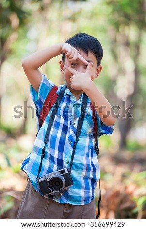 Asian boy with professional digital camera on blurred nature background. Child making frame with hands, taking picture with imaginary camera, selective focus. Outdoors portrait. - stock photo