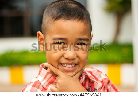 Asian boy with smiling face on blurred background. - stock photo