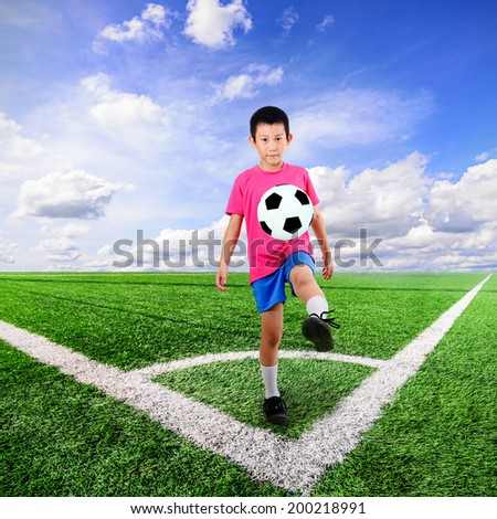 Asian boy with soccer ball at soccer field and blue sky - stock photo